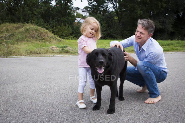 Батько і дочка ласки собаки в саду — стокове фото