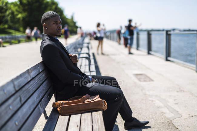 Бизнесмен, сидя на скамейке, глядя на расстоянии — стоковое фото