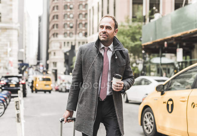 USA, New York City, businessman on the move in Manhattan with coffee to go — Stock Photo