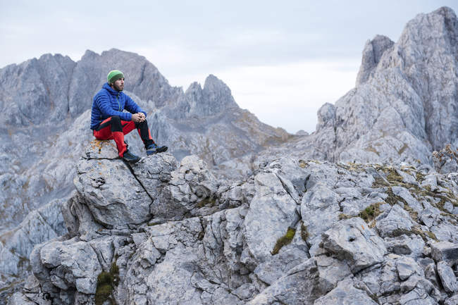 Spain, Picos de Europa, mountaineer resting on rock — Stock Photo