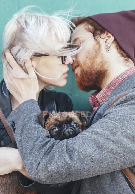 Young couple in love kissing with dog between them — Stock Photo