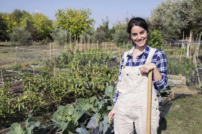 Smiling Female Gardener Standing On Farm And Looking At Camera Stock Photo