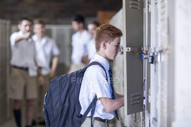 Armadietto di apertura di studente con un gruppo di studenti delle scuole superiori su priorità bassa — Foto stock