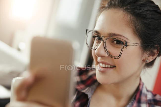 Jeune femme dans des verres avec stylo 3d prenant selfie sur smartphone — Photo de stock