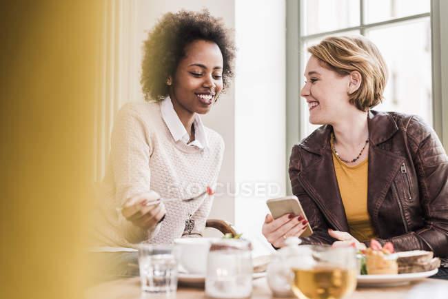 Zwei junge Frauen mit Handy treffen sich in einem Café — Stockfoto