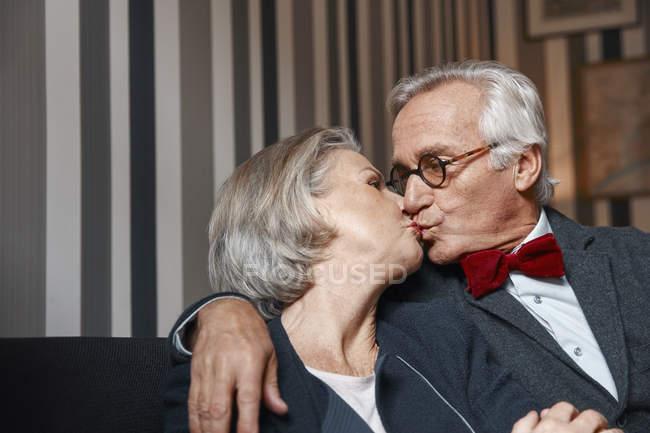 Senior gut gekleidetes Paar küsst auf Couch — Stockfoto