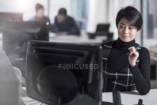 Casual female using computer in modern office — Stock Photo