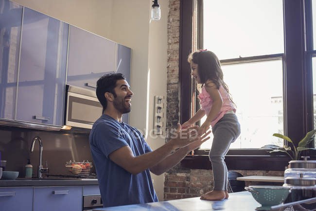 Happy father with daughter playing at domestic kitchen — Stock Photo