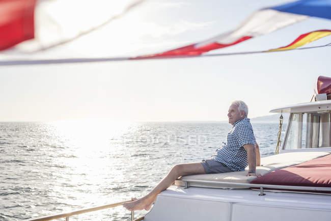 Uomo anziano in gita in barca guardando la vista — Foto stock
