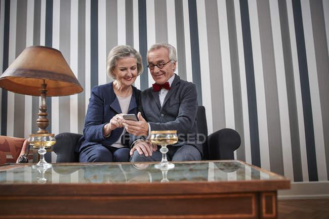 Щаслива пара старший, сидячи на дивані з смартфон — стокове фото