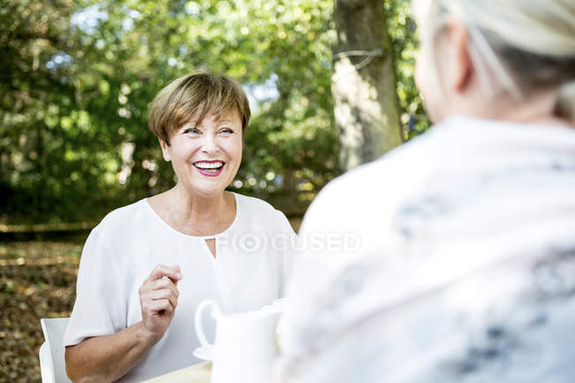 Happy senior woman socializing with friend outdoors — Stock Photo