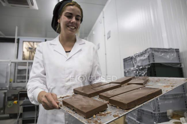 Жінка тримає підношення з Нуга шоколадна в шоколадна фабрика — стокове фото