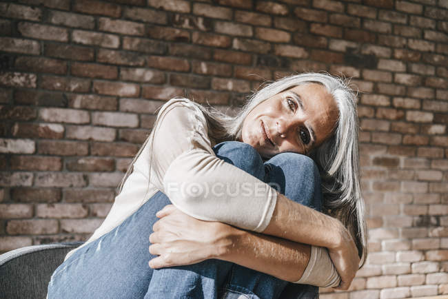 Portrait of woman with long grey hair sitting on chair — Stock Photo