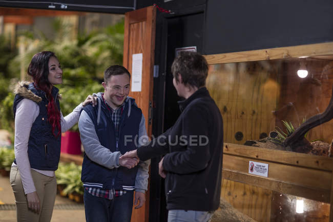 Young man with down syndrome shaking hands with woman at reptile exhibition — Stock Photo