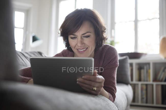 Женщина, лежа на диване у себя дома и с помощью планшета — стоковое фото