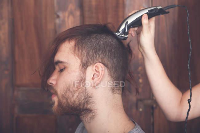 Giovane uomo ottenere un taglio di capelli dalla sua ragazza con macchina per tagliare i capelli — Foto stock