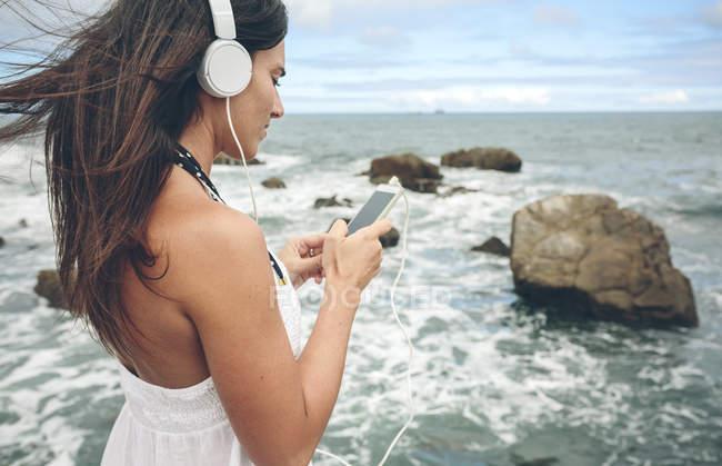 Mulher ouvindo música com fones de ouvido e smartphone em frente ao mar — Fotografia de Stock