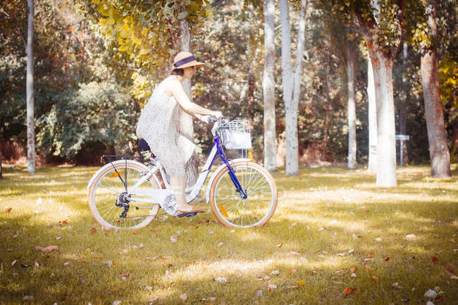 Woman riding bicycle in autumnal park — Stock Photo