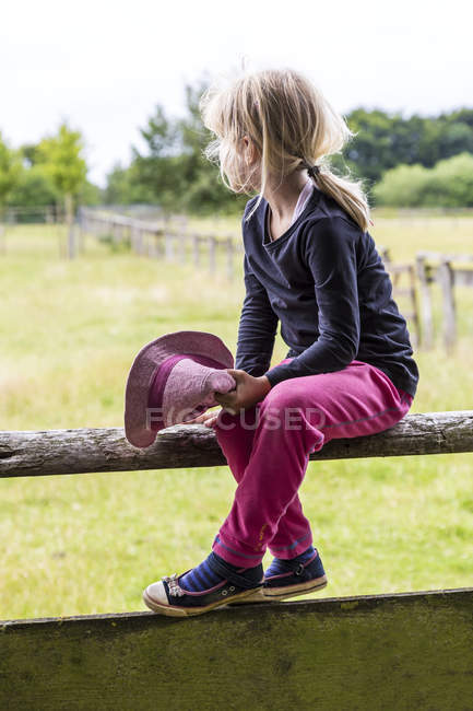 Blond little girl sitting on bar in countryside and looking at distance — Stock Photo