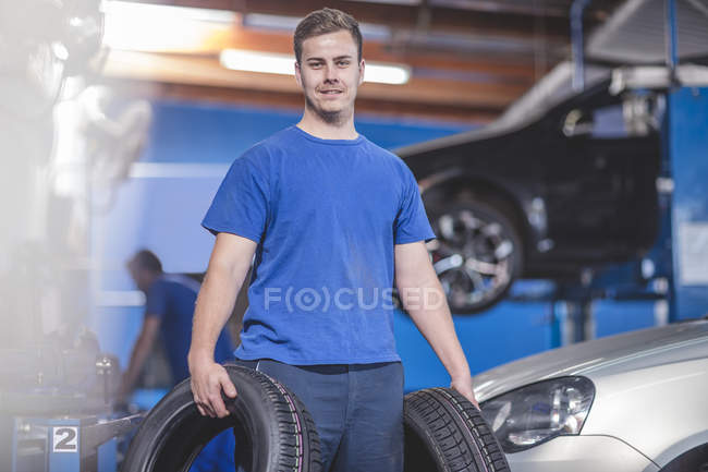Young male mechanic with tyres at workshop — Stock Photo