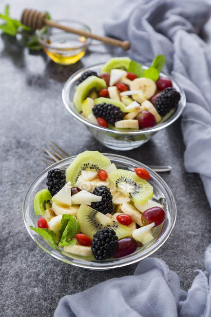 Fruit salad with blackberries in bowls on grey surface — Stock Photo
