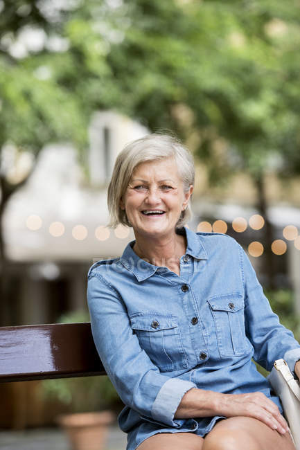 Joyeuse femme adulte âgée assise sur le banc sur fond flou — Photo de stock