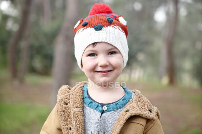 Portrait of smiling boy wearing woolly hat in forest — Stock Photo