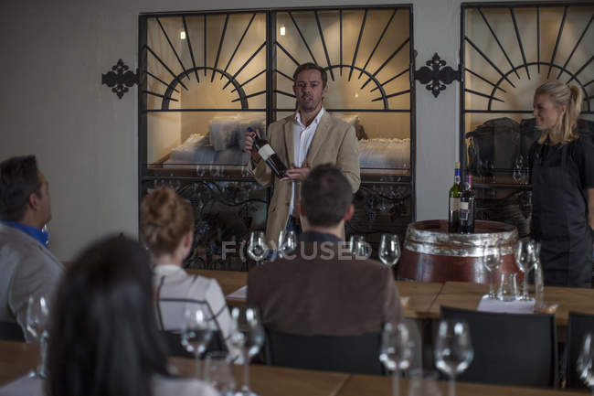 Winemaker and customers at wine degustation in wine estate — Stock Photo