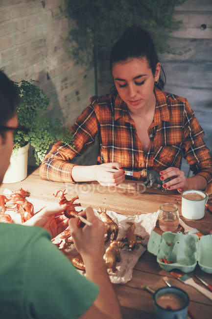 Young couple painting animal figurines with paint — Stock Photo