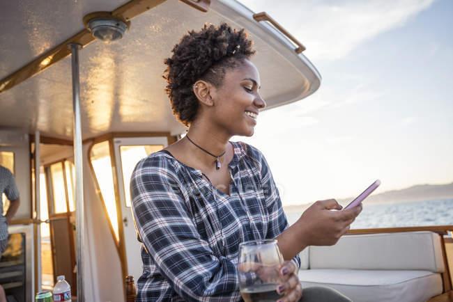 Mujer joven sonriente en un barco revisando el teléfono celular - foto de stock