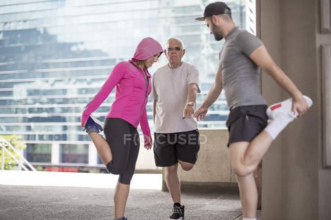 Три спортсмени робить гімнастику у місті — стокове фото