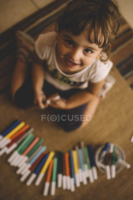 Top view of smiling little girl with many felt tip pens — Stock Photo