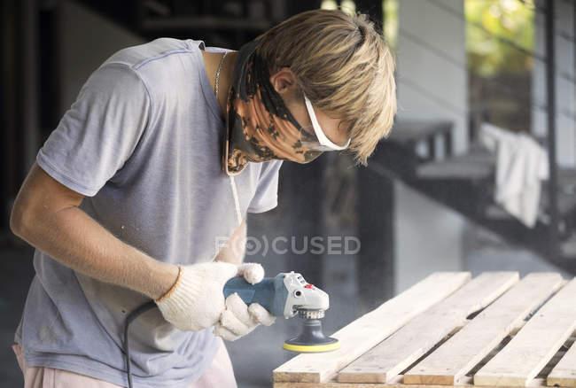 Mann schleift Holz mit einem zufälligen Orbitalschleifer — Stockfoto