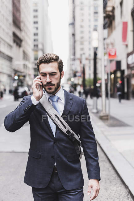 Businessman on cell phone walking on street — Stock Photo