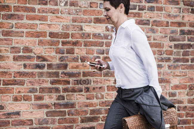Businesswoman running in front of brick wall — Stock Photo