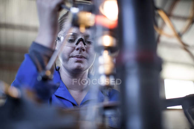 Woman wearing protective glasses operating machine in workshop — Stock Photo