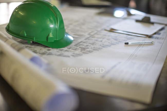 Construction helmet on blueprints in site office — Stock Photo