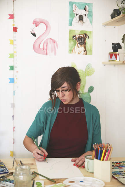 Artist drawing with green pencil on paper — Stock Photo