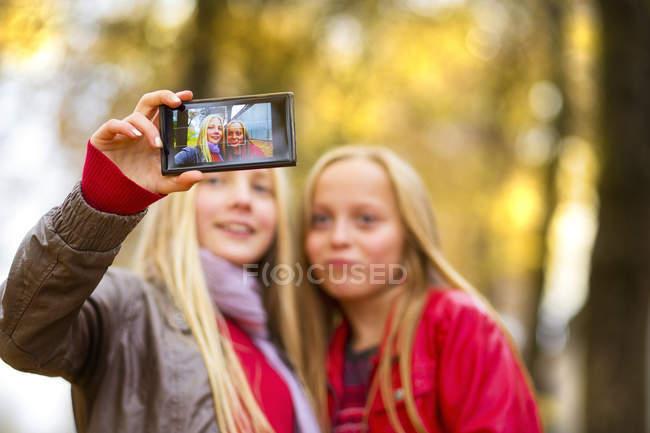 Zwei Mädchen, die die Selfie mit Handy im Herbst — Stockfoto