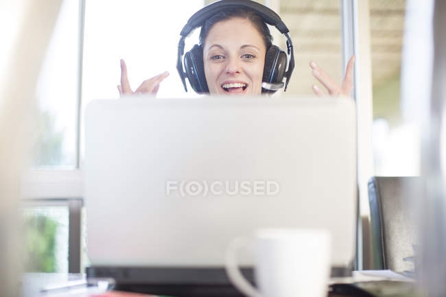 Happy woman at desk with laptop and headset — Stock Photo