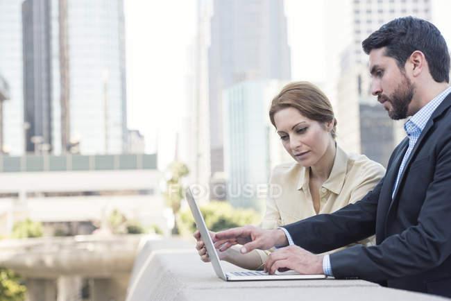 Uomo d'affari e donna d'affari che utilizzano il computer portatile insieme in città — Foto stock