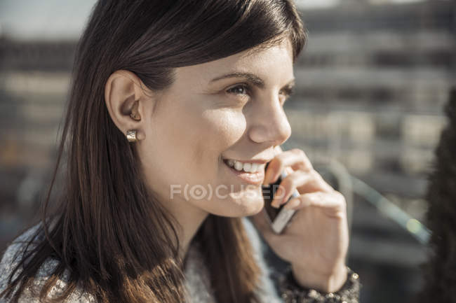 Young woman closeup view with hearing aid in ear and phone — Stock Photo