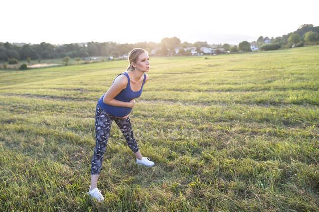 Молодая беременная спортивная женщина делает упражнения на открытом воздухе — стоковое фото