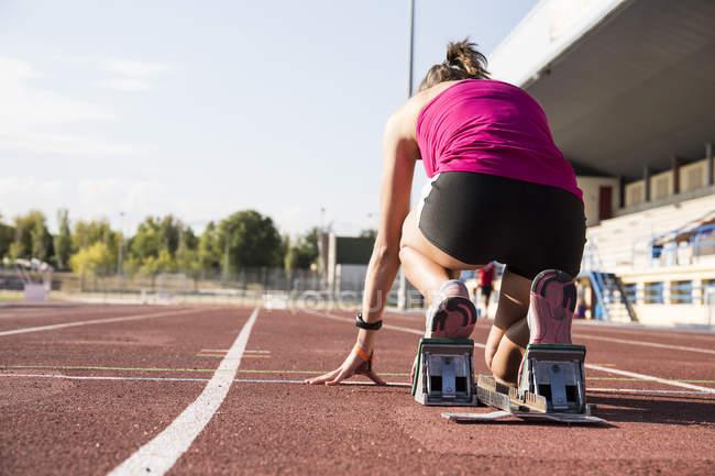 Läuferin auf Tartanbahn in Startposition — Stockfoto