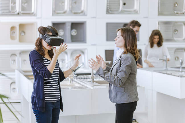 Woman in plumbing shop in virtual reality glasses — Stock Photo