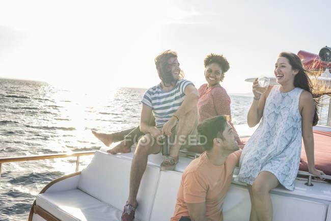 Glückliche Freunde auf eine Bootsfahrt mit einem Drink auf deck — Stockfoto