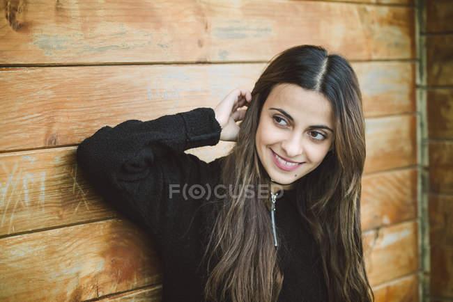 Ritratto di una bella giovane donna su sfondo di legno — Foto stock