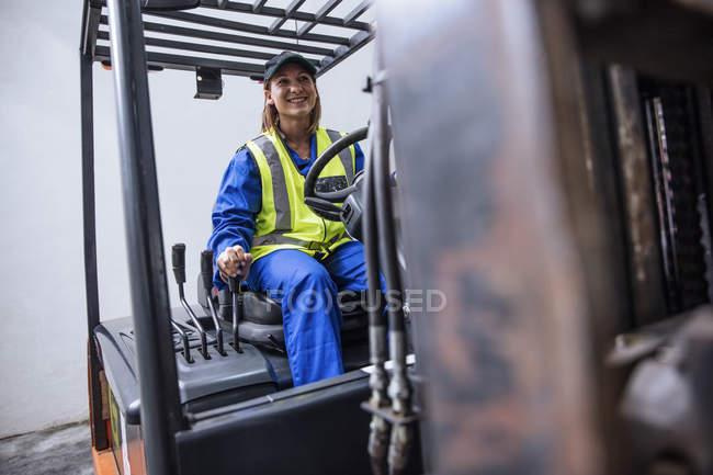 Frau auf Gabelstapler-Maschine trägt Schutzausrüstung und Overall — Stockfoto