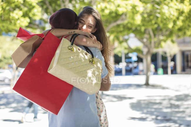 Молодая пара обнимается на улице, девушка держит сумки с покупками — стоковое фото
