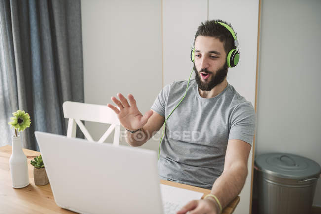 Young man talking to another person through the laptop — Stock Photo